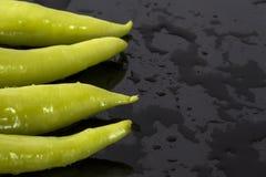 Poivrons verts sur une surface noire humide Photographie stock libre de droits