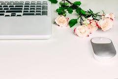 Pojęcie kobiecy workspace z białym laptopem, myszą i pięknymi pastelowymi herbacianymi różami na bielu stole, kosmos kopii zdjęcia stock