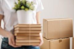 Pojęcie przeniesienie i chodzenie nowy dom W górę, żeńskie ręki trzymają stos książki i zielona roślina w a obrazy stock