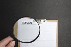 Pojęcie wybierać fachowego kandydata dla pracy Ręka trzyma magnifier i przegląda życiorys zdjęcia royalty free