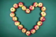 Pojęcie zdrowi owocowi jabłka tworzy kształt hearth na zielonym tle zdjęcia royalty free
