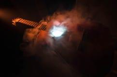 pojęcia gitary elektrycznej ilustraci muzyka Gitara akustyczna odizolowywająca na ciemnym tle pod promieniem światło z dymem z ko Obraz Stock