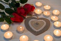 Pojęcia romantyczne, trzy czerwone róże, serce i świeczki, Obrazy Royalty Free