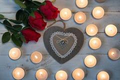 Pojęcia romantyczne, trzy czerwone róże, serce i świeczki, Fotografia Royalty Free