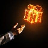 Pojęcie świętowanie z pożarniczym płonącym prezenta symbolem i biznesmen palmą Zdjęcia Royalty Free