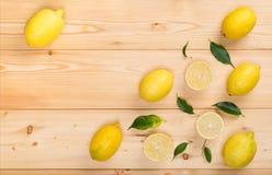 Pojęcie żółte cytryny i ich liście na drewnianym Zdjęcia Stock