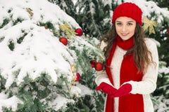 Pojęcie boże narodzenia i nowy rok Zima klimaty Dziewczyna w czerwieni kapeluszowych blisko świątecznej choinki rękawiczkach i obrazy royalty free