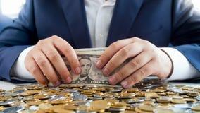 Pojęcie bogactwo i bogactwo Biznesmena obsiadanie za biurkiem zakrywającym z monetami i mieniem duża sterta pieniądze obrazy stock