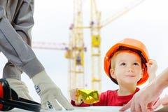 Pojęcie, budowniczowie dyskutuje z dzieckiem nad rysunkiem Hełma ochronnego wyposażenia budowy miasta miejsce, żurawie obrazy royalty free
