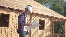 Pojęcie budynek buduje architekta zwolnionego tempa wideo Mężczyzny budowniczy trzyma a w hełmie stoi przy budową zbiory