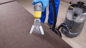 Pojęcie czyścić w biurze i mieszkaniu Suchego cleaning pracownik usuwa brud od kanapy indoors zbiory