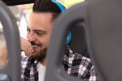 Pojęcie dojeżdżać do pracy, dążenia, podróż Szczęśliwy podróżnik jest ubranym szkockiej kraty koszula słucha muzyka w miasto auto zdjęcia royalty free