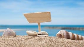 Pojęcie drewniany znak na plaży zakrywającej seashell z błękitem Fotografia Royalty Free