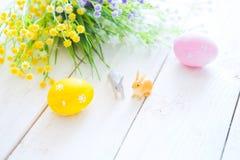 pojęcie Easter szczęśliwy Wielkanocni jajka z kwiatami i małymi królik zabawkami na drewnianej desce, Easter wakacje pojęcie Obrazy Stock