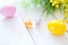 pojęcie Easter szczęśliwy Wielkanocni jajka z kwiatami i małymi królik zabawkami na drewnianej desce, Easter wakacje pojęcie Zdjęcie Stock