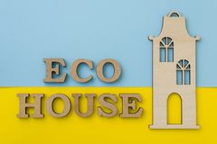 Pojęcie eco budynek mieszkalny Słowa eco dom z żółtym błękitnym tłem, drewniany model dom Obraz Royalty Free