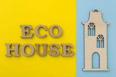 Pojęcie eco budynek mieszkalny Słowa eco dom z żółtym błękitnym tłem, drewniany model dom Obraz Stock
