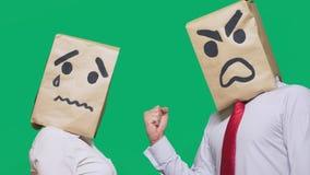 Pojęcie emocje i gesty Dwa ludzie w papierowych torbach z smileys Agresywny smiley przysięga Drugi płacz fotografia stock