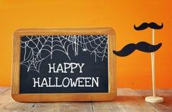 pojęcie kalendarzowej daty Halloween gospodarstwa ponury miniatury szczęśliwa reaper, stanowisko kosy Blackboard obok papierowego Zdjęcie Stock