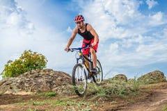 Pojęcie krańcowy kolarstwo, rowerzysta na rowerze górskim na niebieskiego nieba tle, bezpłatna przestrzeń zdjęcie stock
