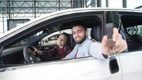 Pojęcie kupienie lub wynajmowanie samochód Młoda szczęśliwa międzyrasowa para z nowymi samochodowymi kluczami zdjęcie wideo