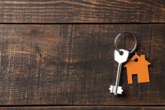 Pojęcie kupować dom Klucze z keychain domem na brązu drewnianym tle na widok z przestrzenią dla inskrypci obrazy stock