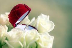 Pojęcie kwiatu pudełko z obrączką ślubną inside wśród biel róż Zdjęcia Royalty Free