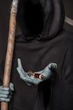 Pojęcie: leka zwłoka Ponurej żniwiarki mienia strzykawka z lekami Zdjęcie Stock