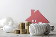 Pojęcie oszczędzanie elektryczność pieniądze, dekoracyjny dom i różne żarówki na lekkim tle, fotografia royalty free