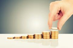 Pojęcie pieniężny przyrost. ręka i złociste monety Fotografia Royalty Free