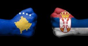Pojęcie powiązania/konflikt między Serbia i Kosowo symbolizującymi dwa przeciwstawiać zaciskać pięściami zdjęcie stock
