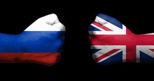 Pojęcie powiązania między Rosja i Zjednoczone Królestwo symbolizującym dwa przeciwstawiać zaciskać pięściami fotografia stock