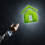 Pojęcie przedstawiający zielonym domem na ciemnym tle eco architektura Obraz Stock
