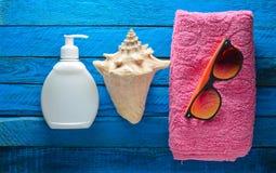 Pojęcie relaksować na plaży Ręcznik, okulary przeciwsłoneczni, sunblock, skorupa na błękitnym drewnianym tle Odgórny widok Obrazy Stock
