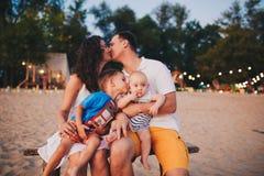 Pojęcie rodzinny wakacje Młody rodzinny obsiadanie na ławce w wieczór na piaskowatej plaży Mama i tata całujemy stary bro zdjęcia stock