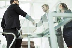 pojęcie rzetelny partnerstwo: uścisk dłoni partnery biznesowi na tle miejsce pracy obrazy royalty free