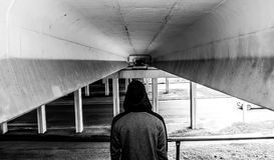 Pojęcie samotność i depresja, niewiadomy osamotniony facet w kapiszonie stoi pod mostem fotografia royalty free