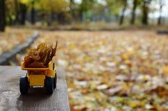 Pojęcie sezonowy zbierać jesień spadać liście przedstawia w postaci zabawkarskiej kolor żółty ciężarówki ładującej z liśćmi znowu obrazy royalty free