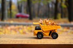 Pojęcie sezonowy zbierać jesień spadać liście przedstawia w postaci zabawkarskiej kolor żółty ciężarówki ładującej z liśćmi znowu obrazy stock