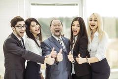 Pojęcie sukces w biznesie: tryumfalna biznes drużyna i szef robimy gest aprobatom obraz royalty free
