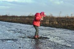 Pojęcie - szczęśliwy dzieciństwo Mała dziewczynka bawić się w kałuży, brudzi buty i moczy, dziecka ` s zabawa, niezapomniani mome Zdjęcia Stock