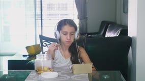 Pojęcie technologia i odtwarzanie Pozytywna radosna nastoletnia dziewczyna relaksuje w domu, siedzący przy stołem w zdjęcie wideo
