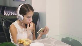 Pojęcie technologia i odtwarzanie Pozytywna radosna nastoletnia dziewczyna relaksuje w domu, siedzący przy stołem w zbiory wideo