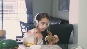 Pojęcie technologia i odtwarzanie Pozytywna radosna nastoletnia dziewczyna relaksuje w domu, siedzący przy stołem w zbiory