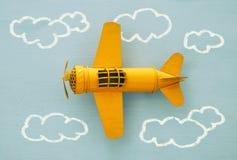 Pojęcie wyobraźnia, twórczość, marzyć i dzieciństwo, Retro zabawka samolot z ewidencyjnymi grafika kreśli na błękitnym tle zdjęcia stock