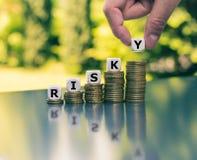 Pojęcie wzrastający wysoki pieniężny ryzyko Kostki do gry umieszczać na wzrastających wysokich stertach monety tworzą słowo obraz stock