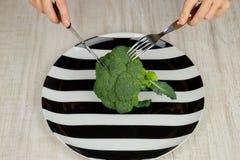 Pojęcie zdrowy żywienioniowy jedzenie zieleń, surowi brokuły kłama na talerzu, kobiet ręki z przyrządami najlepszy widok zdjęcie royalty free