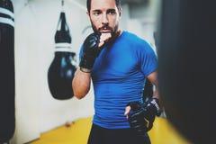 pojęcie zdrowy styl życia Młodego mięśniowego mężczyzna wojownika ćwiczy kopnięcia z uderzać pięścią czarną torbę Kopnięcie bokse Zdjęcia Stock