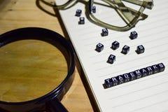 Pojęcie znaki firmowi na drewnianych sześcianach z powiększać - szkło, szklany oko, rezerwuje w rocznika tle zdjęcia royalty free
