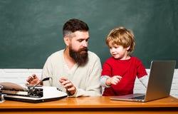 Poj?cie edukacja i nauczanie Nauczycieli pomaga ucznie studiuje na biurkach w sali lekcyjnej kosmos kopii ch?opcy podstawowych do zdjęcie stock